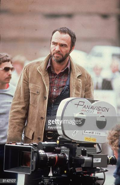American actor Burt Reynolds standing behind a Panavision camera on the set of his latest film