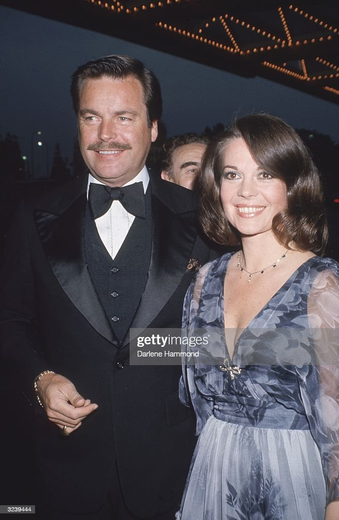 Married American actors Natalie Wood and Robert Wagner attending a formal event. Wood is wearing a blue dress with powder-blue sheer sleeves and a floral top. Wagner is wearing a black tuxedo.