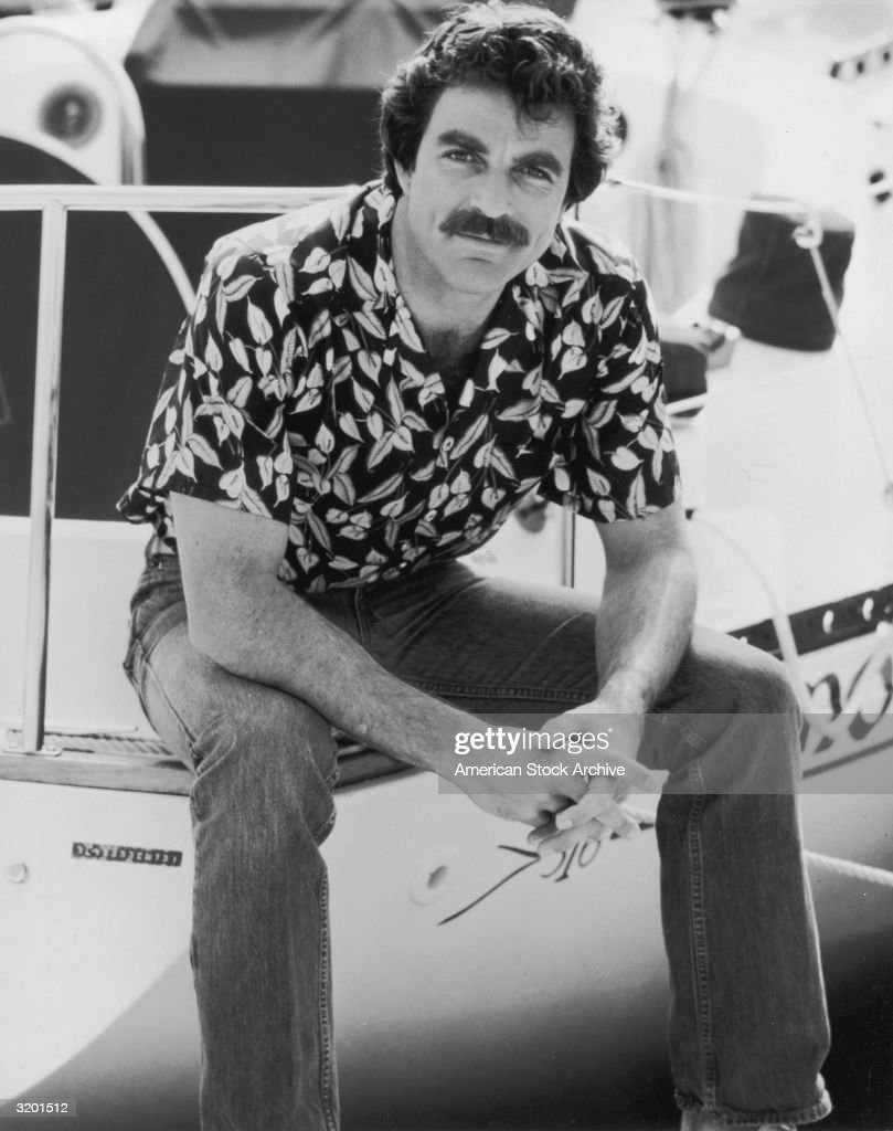 Portrait of American actor Tom Selleck seated on the edge of a boat, wearing a Hawaiian print shirt and jeans.