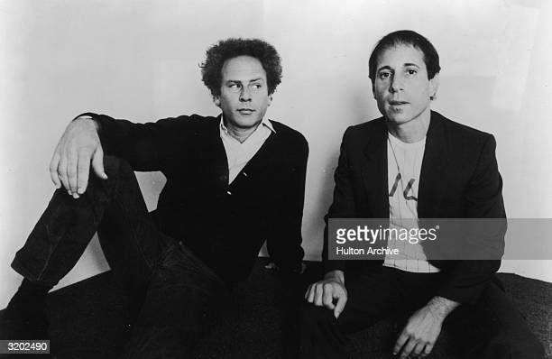 Portrait of American folk rock duo Simon and Garfunkel sitting on a carpet in front of a lightcolored background