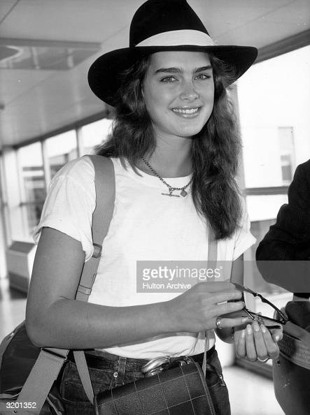 American model and actor Brooke Shields smiles while walking through an airport with her purse and a duffel bag She wears a dark hat with a white...
