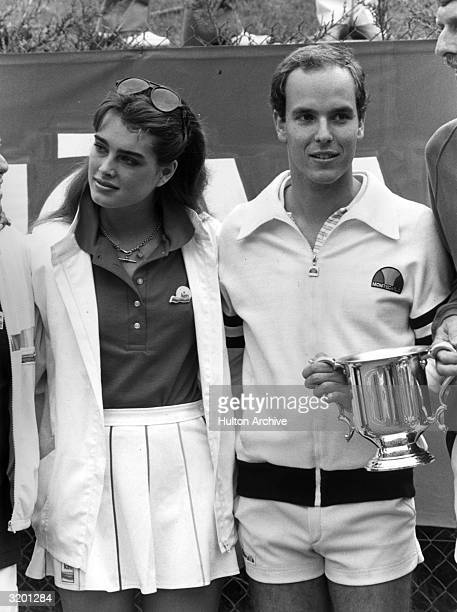 American model and actor Brooke Shields stands with Prince Albert of Monaco The Prince holds a sports trophy cup Both are wearing tennis outfits