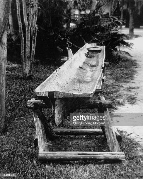 An unfinished dugout canoe made from a hollowedout cypress tree rests on two supports during its construction by the Seminole Indians of southern...