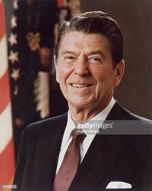 Headshot portrait of the fortieth US president Republican Ronald Reagan smiling in front of the American flag Washington DC