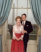 Portrait of U S President Ronald Reagan wearing a brown tie standing behind First Lady Nancy Reagan wearing a pink ruffled blouse and gathered red...