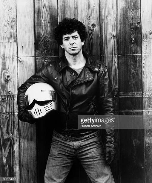 Promotional portrait of American rock singer and songwriter Lou Reed standing in front of a wooden fence holding a motorcycle helmet He wears a black...