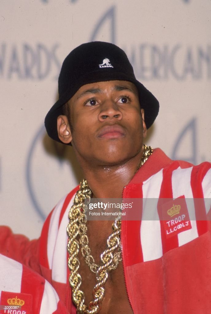 A candid portrait of rapper LL Cool J wearing a black Kangol hat large gold chain necklaces and a redandwhite warmup jacket at the American Music...