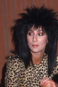 A headshot of American pop singer and actor Cher wearing a black spikey wig and a cheetah print top