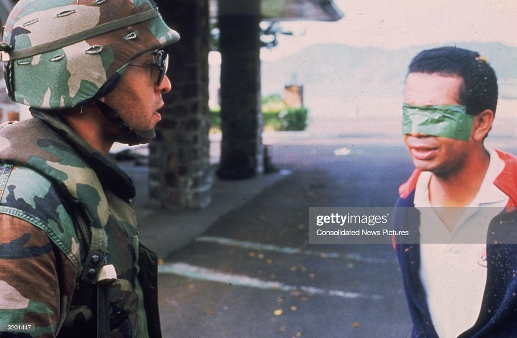 An American soldier stands in the street with a blindfolded Panamanian prisoner during the United States invasion, 'Operation Just Cause,' to oust Panamanian leader General Manuel Noriega, Panama. The prisoner has green duct tape over his eyes. Former CIA informant Noriega was arrested and tried in the U.S. for drug trafficking, money laundering, and racketeering. He was sentenced to 40 years in prison.