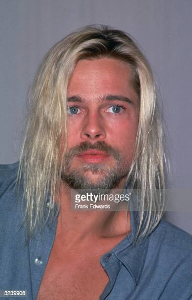 Headshot of American actor Brad Pitt with long dyed blonde hair wearing an open collared blue shirt