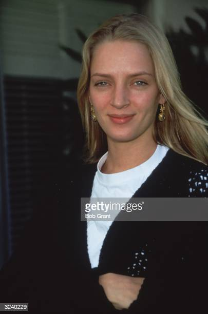American actor Uma Thurman wearing a white tshirt and a black sweater smiling outdoors