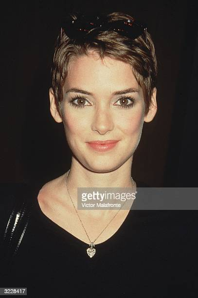Headshot of American actor Winona Ryder smiling in a black sweater and a heartshaped locket New York City