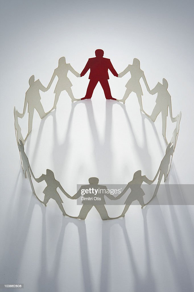 Circle of cut-out figures with one man in red : Stock Photo