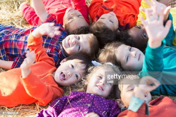 Circle of multi-ethnic children lying on backs