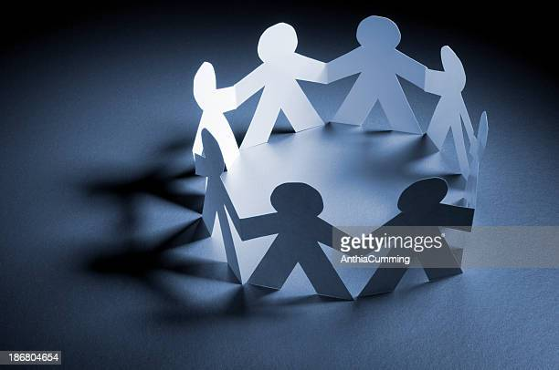 Circle of paper chain people holding hands in spotlight
