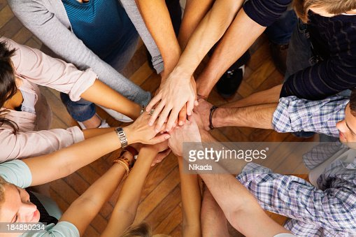 Circle of people with their hands in the center