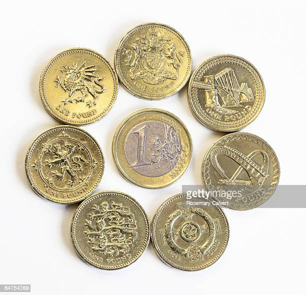 Circle of pound coins with one euro in centre.