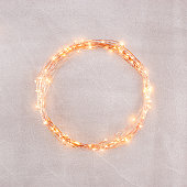 Circle yellow glow led garland on the concrete wall. Background with copy space.