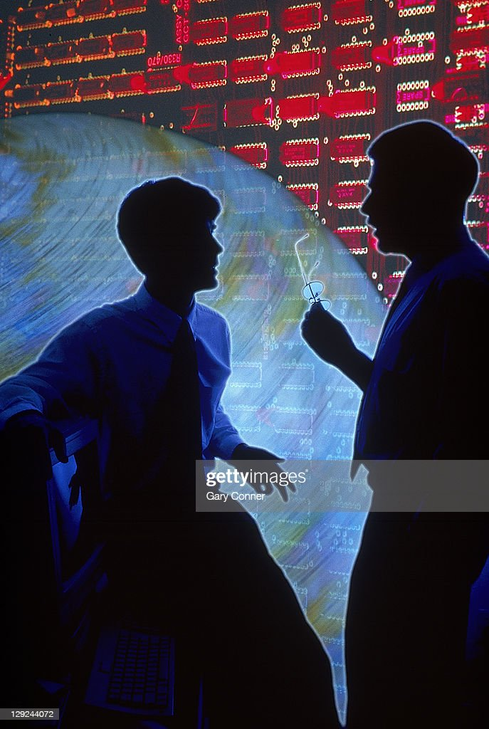 Circuit boards and silhouette of businessmen talki : Stock Photo