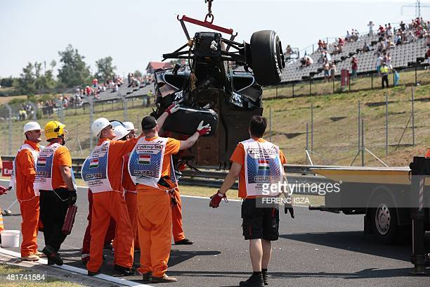 Circuit marshals remove the crashed car of Sahara Force India F1 Team's Mexican driver Sergio Perez from the circuit during the first practice...