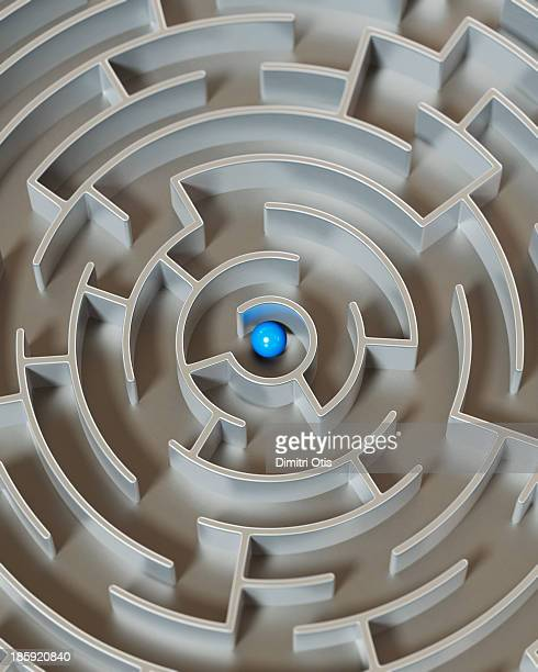 Circular metal maze with blue ball in centre