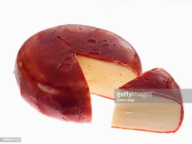 Circular round dutch edam cheese covered in red wax protection and slice cut out