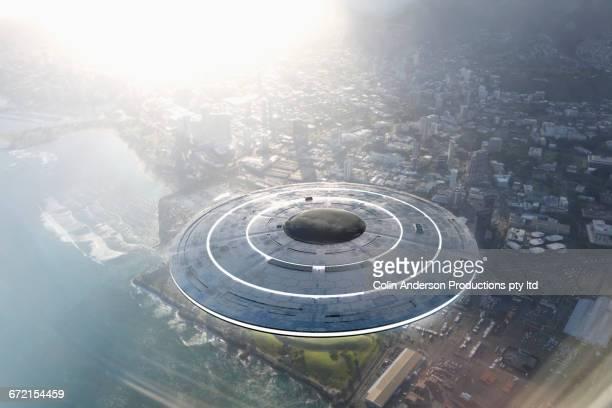 Circular UFO flying over city