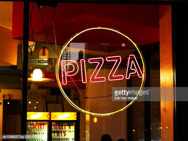 Circular yellow and red pizza sign in window of restaurant