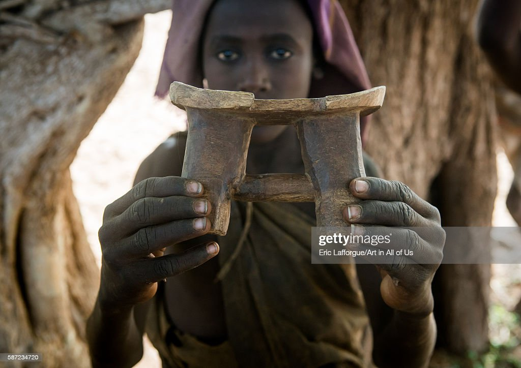 Circumcised boy from the dassanech tribe with his traditional wooden seat omo valley omorate Ethiopia on March 21 2016 in Omorate Ethiopia