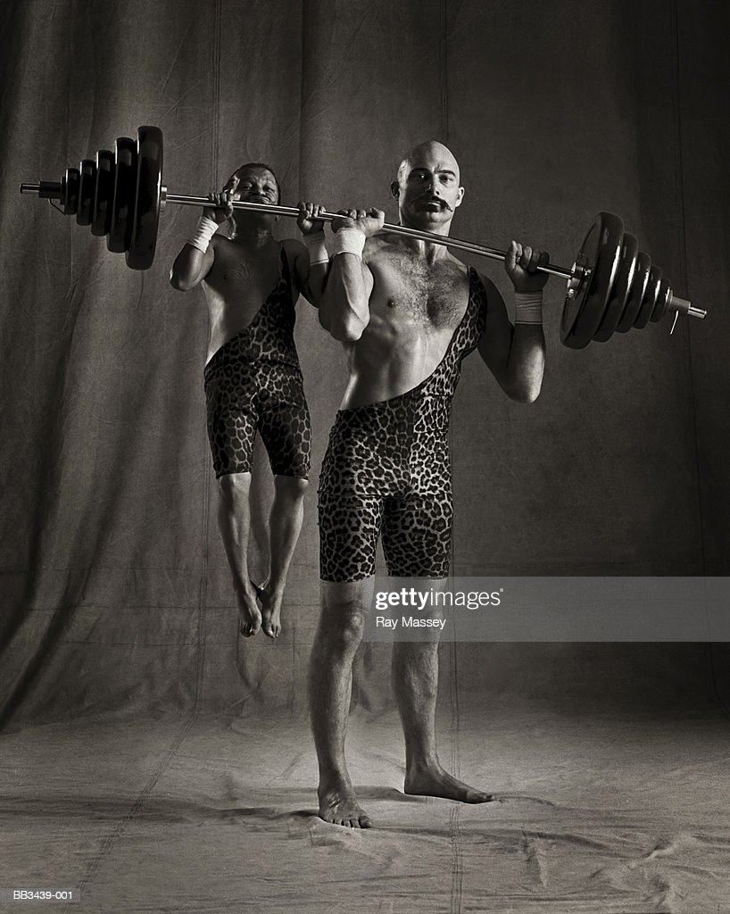 Circus dwarf hanging from barbell lifted by strongman (tinted B&W) : Stock Photo