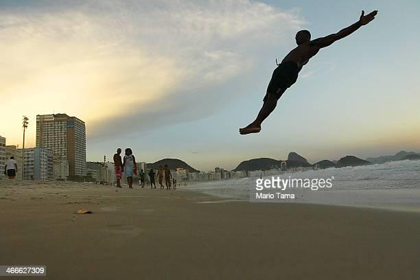 Circus performer Maicon Gomes does a set of flips for his friends on Copacabana Beach following the Alegria da Zona Sul preCarnival street parade on...