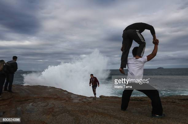 Circus performers practice a pose on Arpoador rock during strong winter swells on the Atlantic Ocean on August 11 2017 in Rio de Janeiro Brazil Waves...