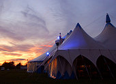 A Circus Tent Lit With Twilight and Blue Neon.