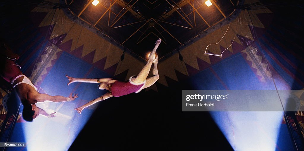 Circus trapeze act, woman in mid-leap,low angle view (Composite) : Stock Photo