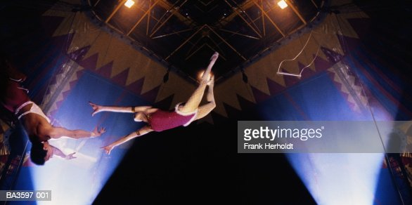 Circus trapeze act, woman in mid-leap,low angle view (Composite) : Bildbanksbilder
