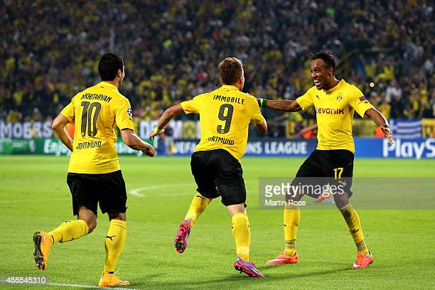 Ciro Immobile of Borussia Dortmund is congratulated by teammates Henrikh Mkhitaryan and PierreEmerick Aubameyang of Borussia Dortmund after scoring...