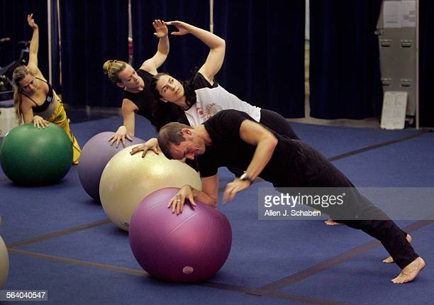 Cirque du Soleil artist Chris Baraniuk front who is a coach of two acts performs pilates–based movements focusing on core strength with fellow...