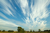 White cirrus clouds in a blue sky over farmland in Northamptonshire.