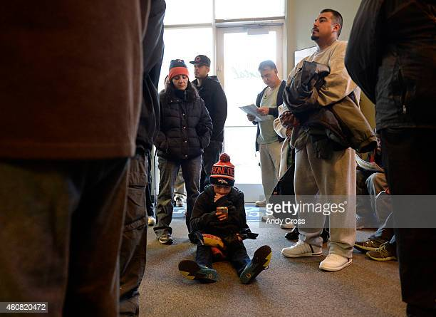 Cisco Gonzales checks his phone as his mother Claudia upper left waits patiently for her son to be seen by a dentist at Comfort Dental on west 38th...