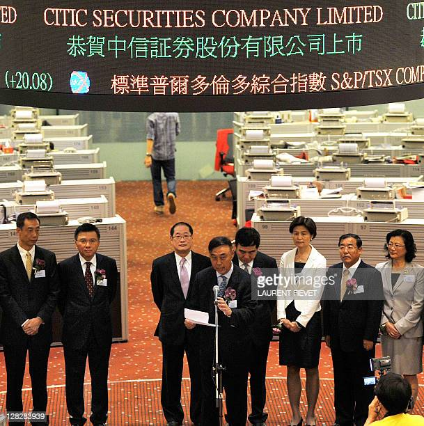 Citic Securities chairman Wang Dongming speaks to traders on the floor of the Hong Kong Stock Exchange during the company's IPO launch in Hong Kong...