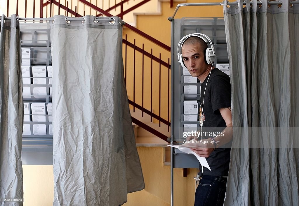 A citizen goes out of a polling booth to cast his ballot at a polling station during the Spanish general election in Madrid, Spain on June 26, 2016.