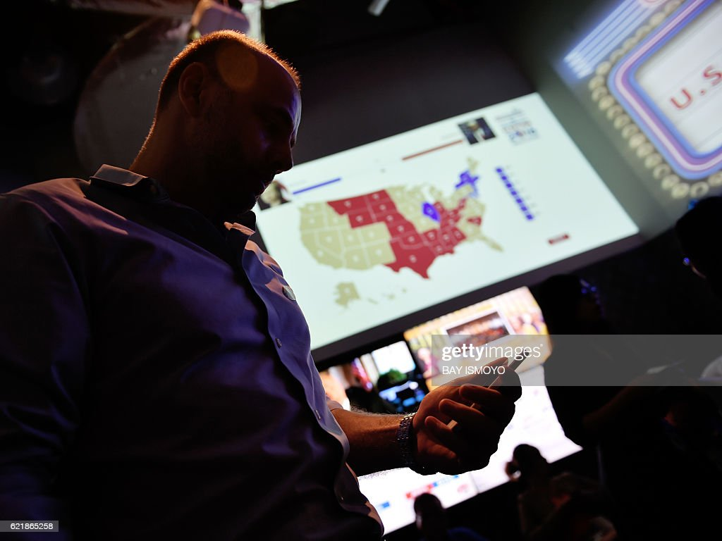 A US Citizen Looks At His Phone Past A US Electoral Map As He And - Past election map us