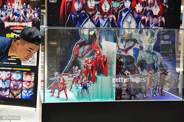 A citizen looks small Ultraman models displayed in a shopping mall on May 3 2016 in Shanghai China As part of an exhibition commemorating 50th...