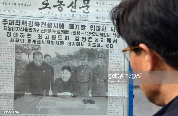 A citizen of Pyongyang looks at the Rodong Sinmun newspaper on May 15 2017 The leading newspaper of North Korea reported that the country...