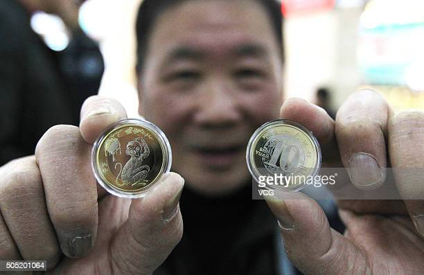 A citizen shows his Monkey commemorative coins exchanged at a branch of Agricultural Bank of China on January 16 2016 in Wenzhou Zhejiang Province of...