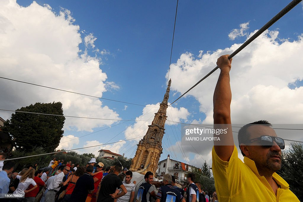 Citizen take part in a procession to carry a 25 meters wheat obelisk build in honor of Madonna Addolorata (Our Lady Of Sorrows) during a farmer festival in Mirabella Eclano, south of Italy on September 14, 2013. The ancient farmer festival (Medium Eve) after 900 years of stop, restart in XVI age to protect the hard work of farmers like religious festival in honour of the Lady Of Sorrows. 12 Oxen carry the obelisk and all the Mirabella Eclano citizens pull the ropes to balance the obelisk during the slow run.