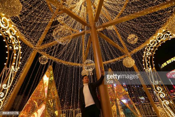 A citizen takes selfie with a 22metrehigh Christmas tree decorated with golden LEDs to welcome Christmas at Qibao Ancient Town on December 11 2017 in...