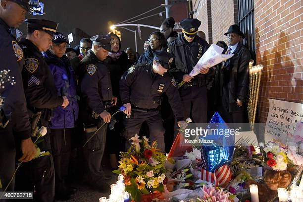 Citizens and NYPD officers attend a candlelight vigil for slain NYPD officers Wenjian Liu and Rafael Ramos on December 21 2014 in the...