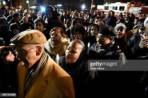 Citizens attend a candlelight vigil for slain NYPD officers Wenjian Liu and Rafael Ramos on December 21 2014 in the BedfordStuyvesant neighborhood of...