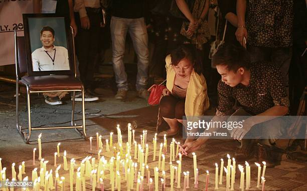 Citizens from north eastern states of India staging a candle light protest to condemn murder of Manipuri youth at Jantar Mantar on July 22 2014 in...